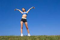 青空のもとで伸びをする女性
