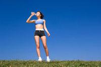 青空のもとで水を飲む女性