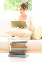 ソファに座り読書する女性