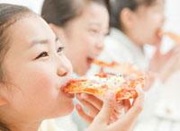 ピザを食べる小学生の女の子