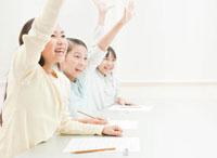 元気よく手を上げる小学生の女の子3人