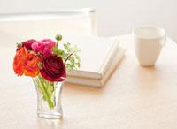 食卓の上に飾られた花と本とカップ
