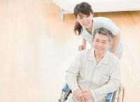 車椅子に座るシニア男性と女性介護士