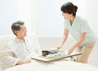 シニア男性に食事を運ぶ介護士
