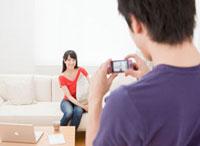 コンパクトデジタルカメラで写真を撮る夫