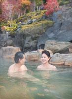 露天風呂に入る60代の夫婦と紅葉