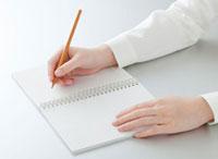 ノートに書きこむ女性の手
