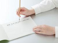 毛筆で手紙を書く女性の手
