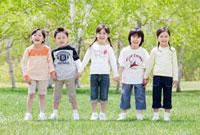 新緑の中で手をつなぐ5人の子供