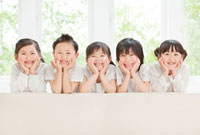 ソファーから顔を出す5人の子供