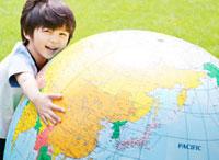 大きな地球儀を抱える男の子