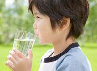 新緑の中で水を飲む男の子