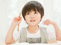 鉛筆を持って上を見上げる男の子