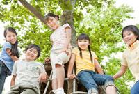 木の遊具に座る5人の小学生