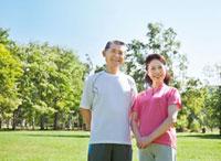 緑の中で佇むトレーニングウェアの60代シニア夫婦