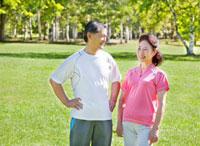 緑の中で談笑するトレーニングウェアの60代シニア夫婦