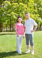 緑の中で佇むトレーニングウェアの60代シニア夫婦 10208001157| 写真素材・ストックフォト・画像・イラスト素材|アマナイメージズ