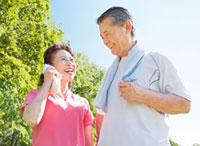 緑の中で笑うトレーニングウェアの60代シニア夫婦