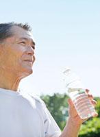 水を飲むトレーニングウェアの60代シニア男性