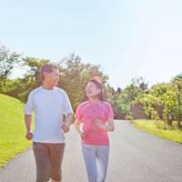 ウォーキングするトレーニングウェアの60代シニア夫婦