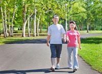 緑の中でウォーキングするトレーニングウェアの60代シニア夫婦