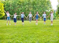 緑の中で手をつなぎジャンプする7人の小学生の男の子と女の子