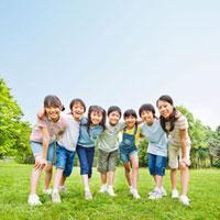 緑の中で肩を組む7人の小学生の男の子と女の子