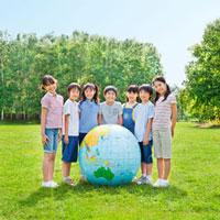 緑の中で地球儀を囲む7人の小学生の男の子と女の子