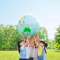 緑の中 地球儀を持ち上げる小学生の男の子と女の子