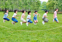 緑の中 大縄跳びをする7人の小学生の男の子と女の子