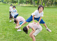 緑の中 馬跳びをする小学生の男の子と女の子