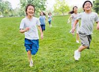 緑の中を走る小学生の男の子と女の子