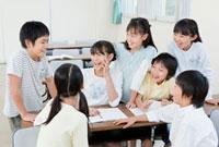 教室で談笑する7人の小学生の男の子と女の子