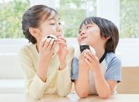おにぎりを食べる女の子と男の子の姉弟