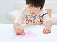 クレヨンでハートの絵を描く男の子