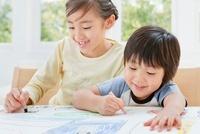 クレヨンで絵を描く女の子と男の子の姉弟