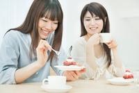 お茶とケーキを楽しむ2人の20代女性