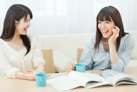 カタログを見ながら会話を楽しむ2人の20代女性