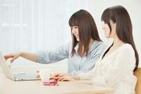 ノートパソコンを操作する2人の20代女性