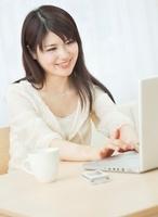 ノートパソコンを操作する20代女性