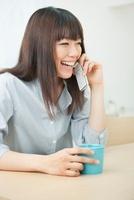 携帯電話で話す20代女性