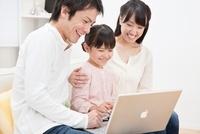 ソファーでパソコンを操作する家族