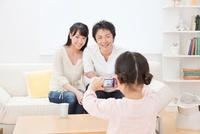 ソファーに座る父と母をコンパクトデジタルカメラで撮影する子