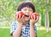 緑の中、採れたてのトマトを持つ男の子