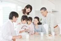 リビングでiPadを操作する三世代家族