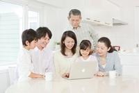 リビングでパソコンを操作する三世代家族