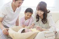 ソファーで赤ちゃんを見守る家族