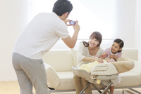 コンパクトデジタルカメラで母と子の写真を撮る父 リビング