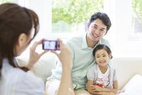 コンパクトデジタルカメラで父と子の写真を撮る母 リビング