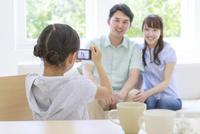 コンパクトデジタルカメラで両親の写真を撮る子 リビング